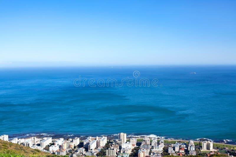 Stadtküste mit weißer Hausansicht über blauen See- und Himmelhintergrund in Cape Town, Südafrika lizenzfreie stockbilder
