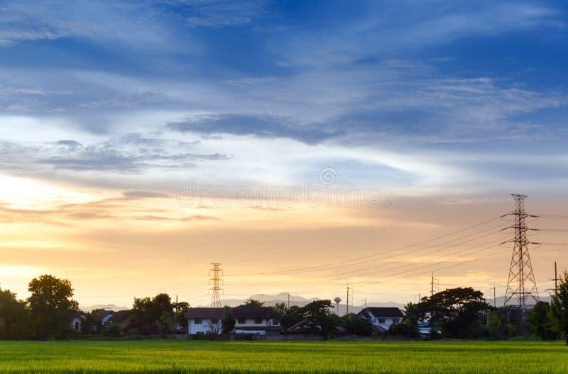 Stadtlandschaftsansichtsonnenuntergang über der Reisfeldplantage, die mit Haus und Telekommunikation bewirtschaftet lizenzfreie stockfotos