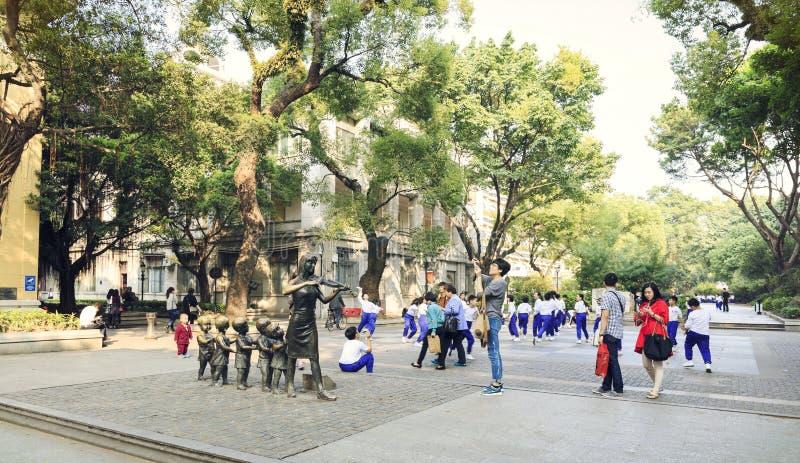 Stadtnachbarschaftspark, Gemeinschaftsgarten mit Statuen, Fußgänger und Gruppe Kinder in China lizenzfreie stockbilder