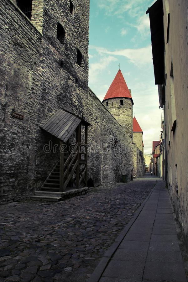 Stadtstraße der alten Stadt in Tallinn mit einer alten Wand des Kalksteins und der roten Ziegeldächer auf den Türmen stockfotografie