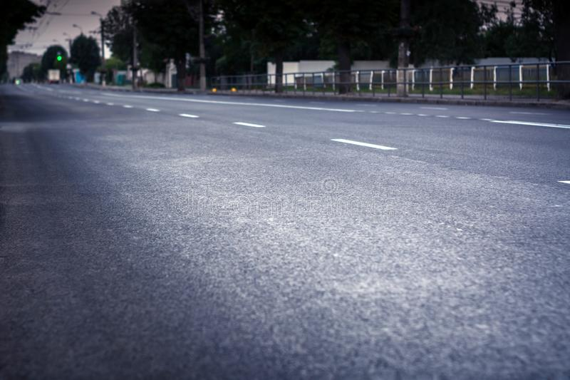 Stadtstraße mit neuem Asphalt Entlang es gibt es eine Gasse Ampeln und Autos sind sichtbar lizenzfreie stockfotografie