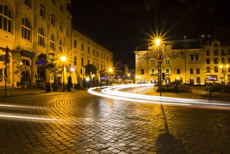 Stadtstraße mit unscharfen Lichtern von den Scheinwerfern von Autos lizenzfreies stockbild