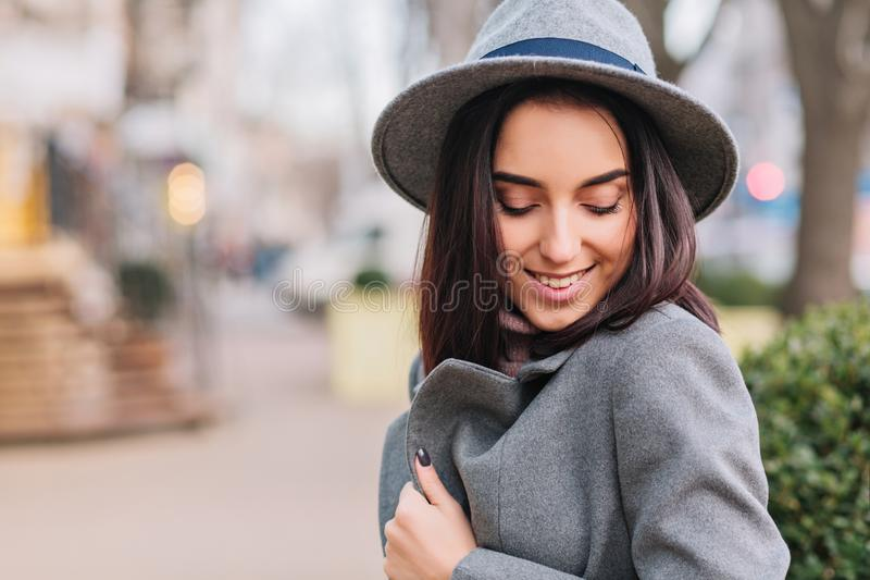 Stadtwegzeit des Bezauberns der jungen stilvollen Frau im grauen Mantel, Hut gehend auf Straße in der Stadt L?cheln mit geschloss stockfoto