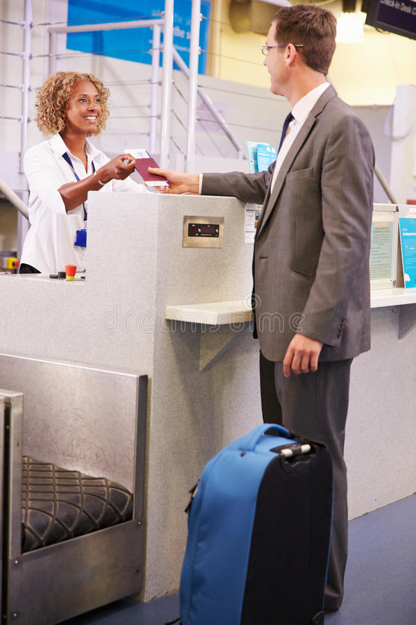 Staff At Airport Check In Desk Handing Ticket To Businessman royalty free stock photos