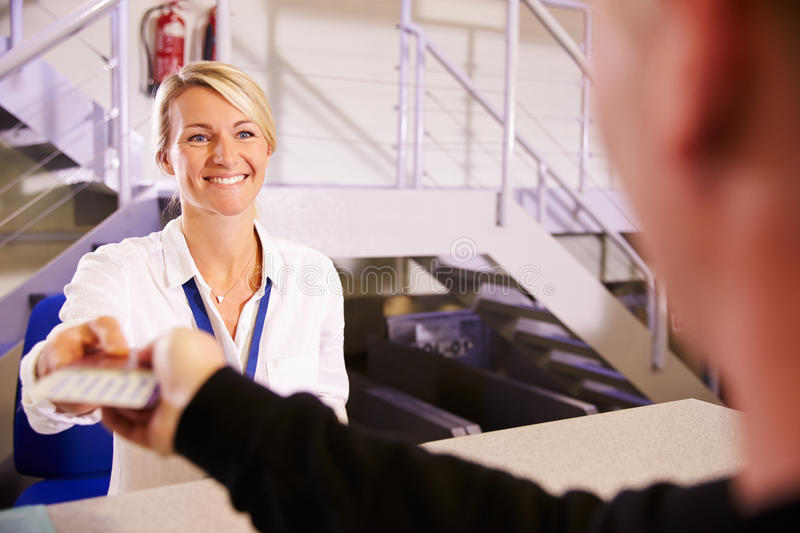 Staff At Airport Check In Desk Handing Ticket To Passenger royalty free stock image
