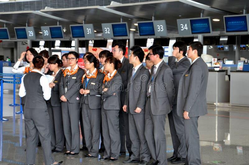 Staff briefing at Shanghai Pudong International airport. Shanghai, China - February 21, 2013: Counter staff line up for a briefing at Shanghai's Pudong stock photos