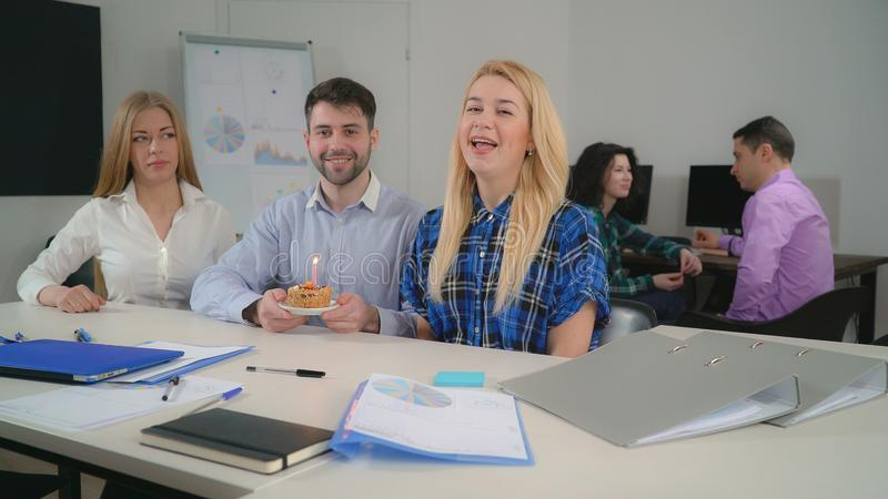 Staff celebrating birthday in office. Coworkers wish a happy birthday with cake and candle. Employees enjoy party singing song in meeting room. Young people in stock images