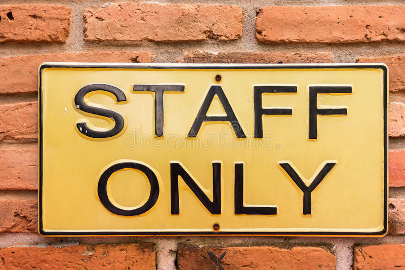 Staff only on license plate. Staff only on yellow license plate on red brick wall stock images