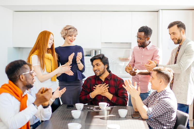 Staff members are congratulating their Indian colleague who has a promotion. Closeup portrait royalty free stock photo
