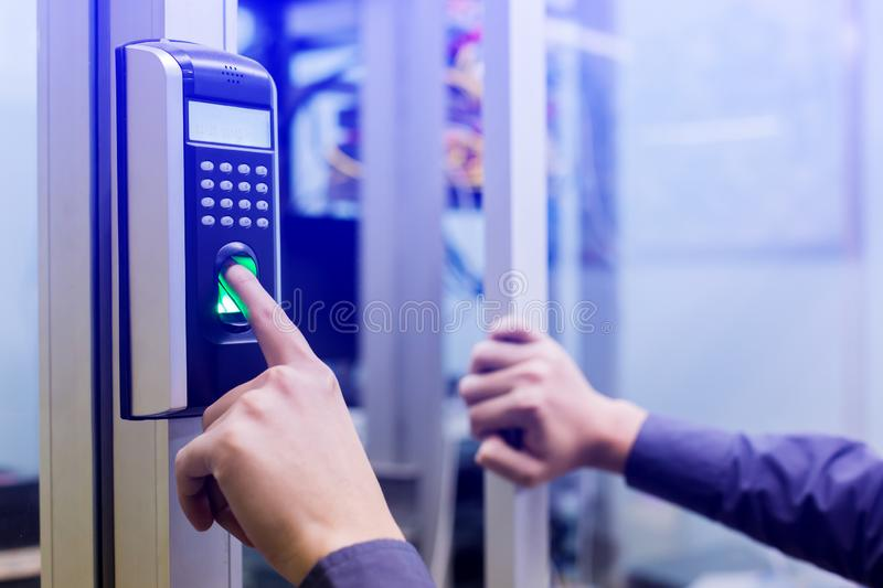 Staff push down electronic control machine with finger scan to access the door of control room or data center. The concept of data. Security or data access royalty free stock photo