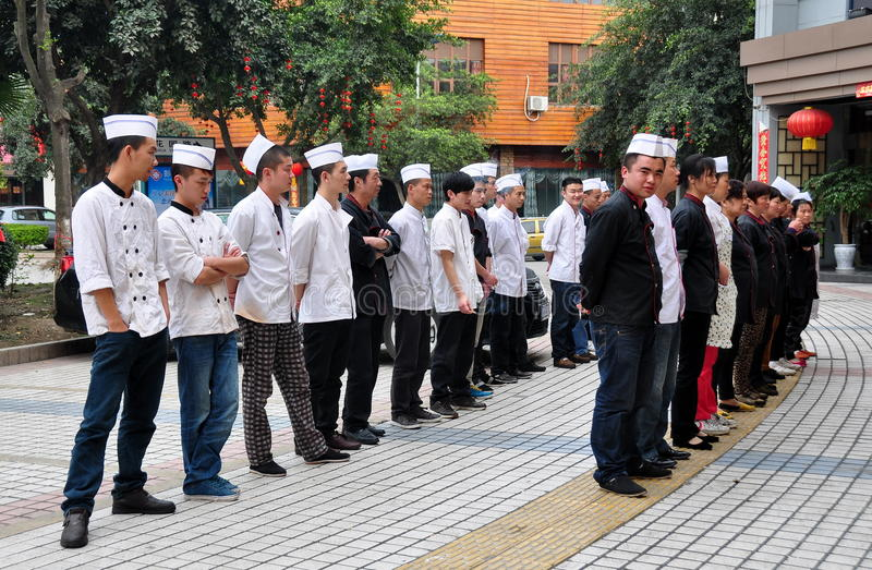 Pengzhou, China: Restaurant Staff Briefing. The staff of s large restaurant stands outside before the dinner service for roll call and last-minute briefing stock photography