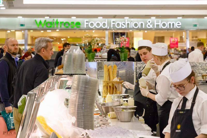 Staff serving customers at a food bar in Canary Wharf with Waitrose supermarkets in the background. London, UK - June 25, 2017 - Staff serving customers at a stock photos