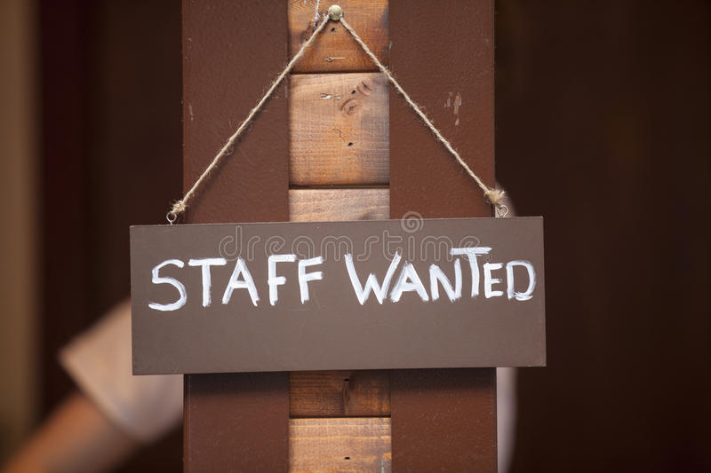 Staff Wanted Sign. Staff wanted inscription on a board hanging on wooden post stock images
