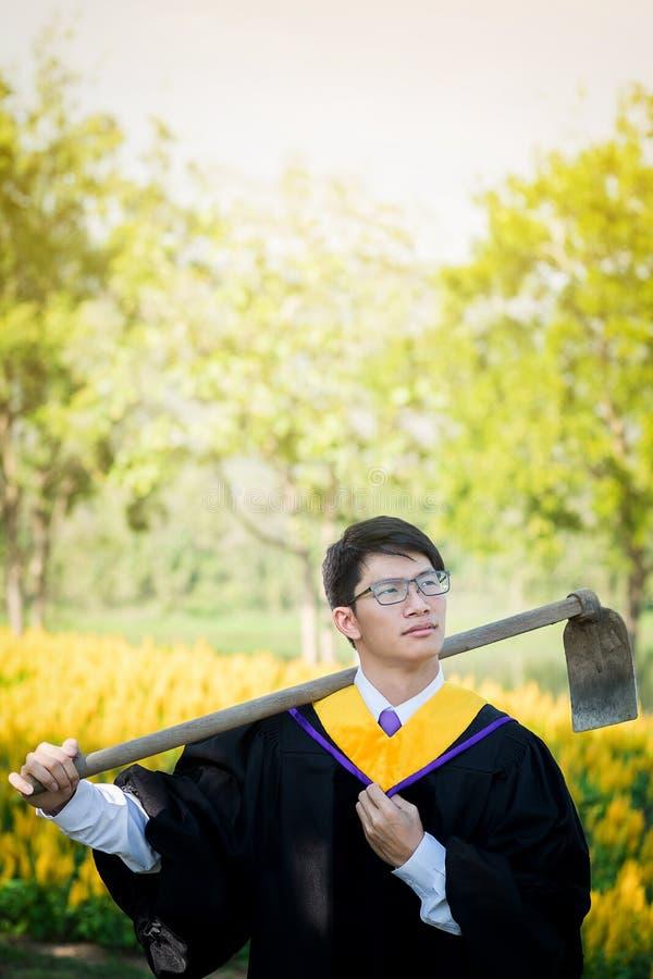 Staffelung: Student Standing, das eine Schaufel mit Diplom mit trägt stockfotografie