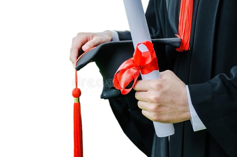 Staffelungs-, Studentengriffhüte und Diplom in der Hand während der Anfangserfolgsabsolvent der Universität stockfoto