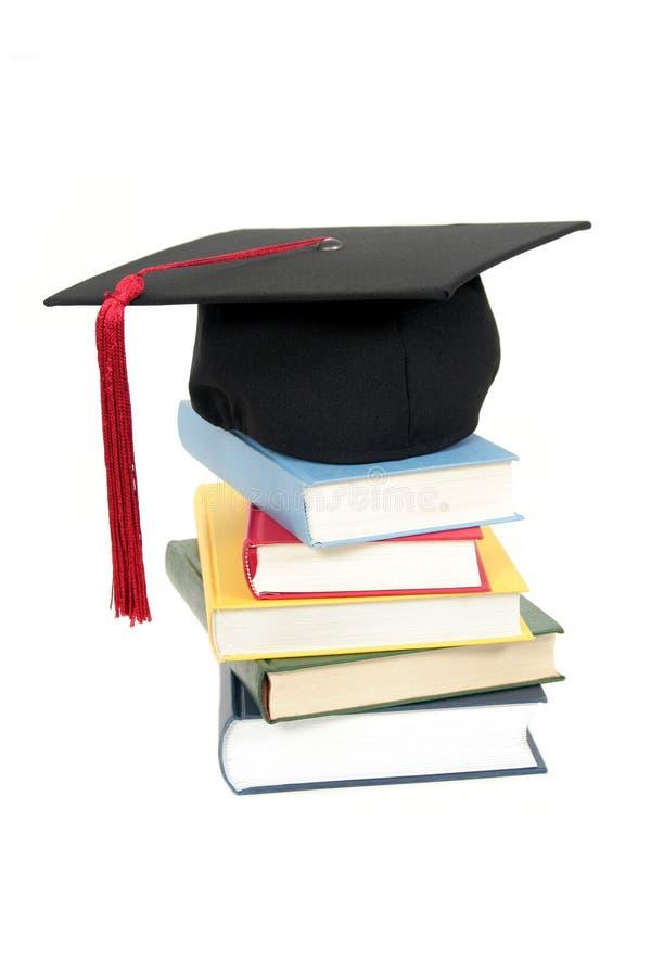 Staffelungschutzkappe auf Stapel Büchern stockfotografie