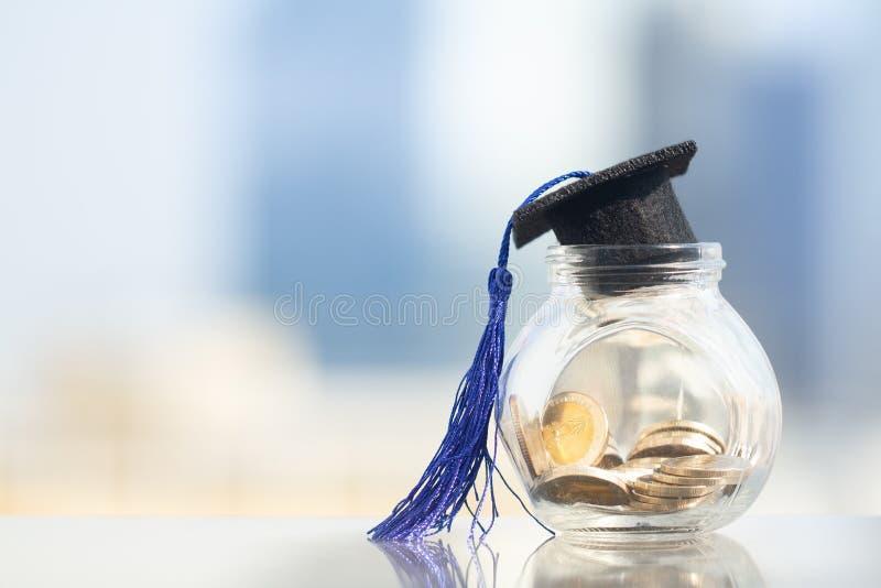 Staffelungshut mit blauer Quaste auf Glasgefäß oder Sparschwein lizenzfreies stockfoto