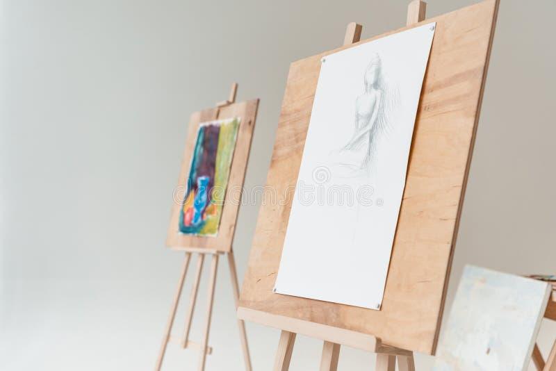 staffli med konstnärliga målningar i tom konststudio arkivfoto