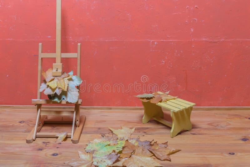 Staffliställning med torkade sidor, den lilla bänken och torkade sidor på golv i studio f?r garneringdruvor f?r h?st kastanjebrun royaltyfri foto