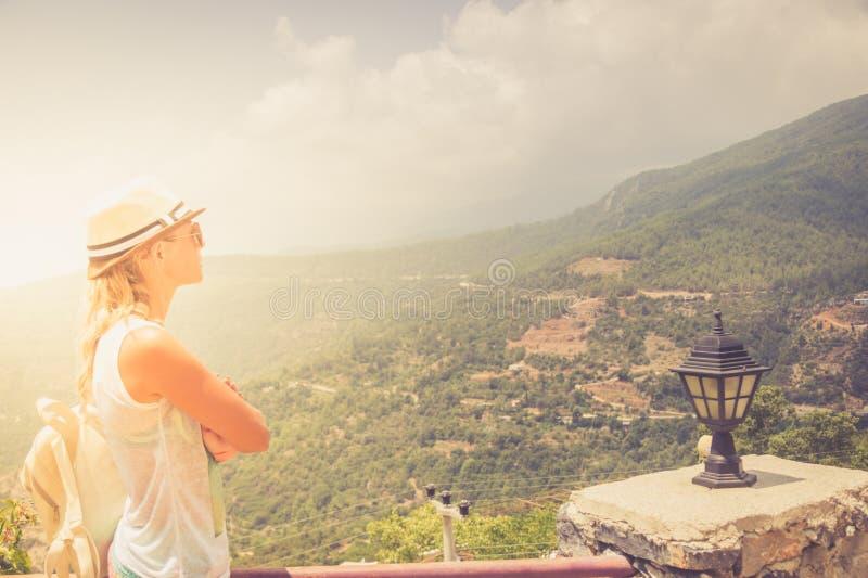 Stag för ung kvinna på kanten av klippan som ser över expansiv sikt av slättar och berg royaltyfri fotografi