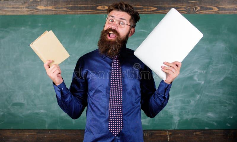 Stag som är modernt med teknologi Lärare uppsökte hipsterhåll bok och bärbar dator Modern teknologifördel lärare arkivfoton