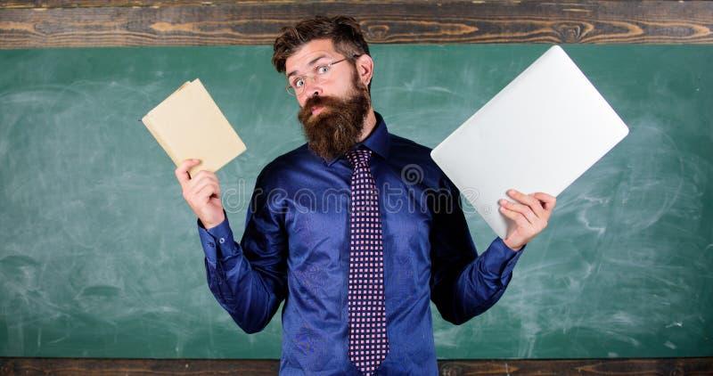 Stag som är modernt med teknologi Lärare uppsökte hipsterhåll bok och bärbar dator Modern teknologifördel Digital mot royaltyfri bild