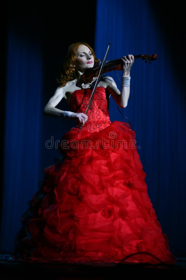 On stage - beautiful, frail and slender girl with fiery red hair - a well-known musician, virtuoso violinist Maria Bessonova. royalty free stock photos