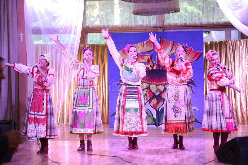 On the stage beautiful girls in national Russian costumes, gowns sundresses with vibrant embroidery - folk-music group the Wheel. stock image