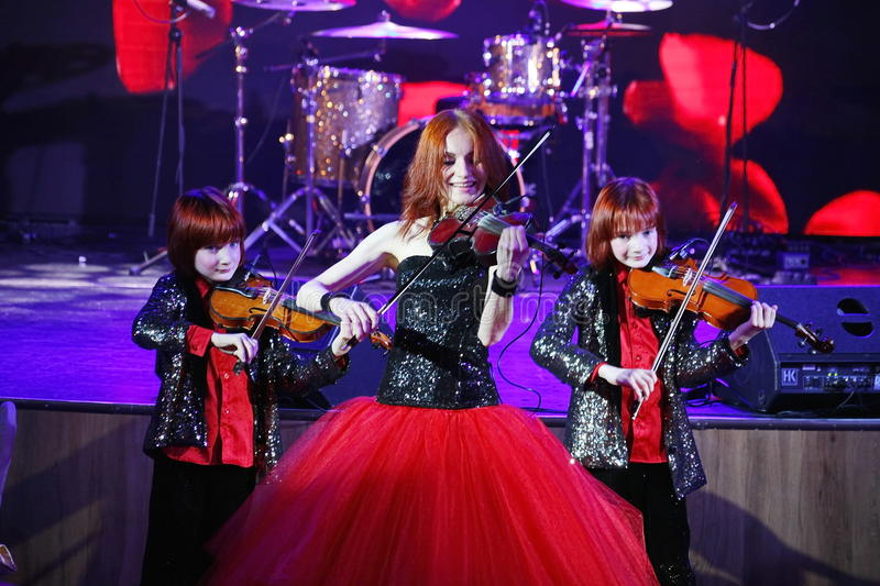On stage, the expressive red-haired violinist Maria Bessonova sons twins. violin trio two generations of red fiery musicians. royalty free stock photography