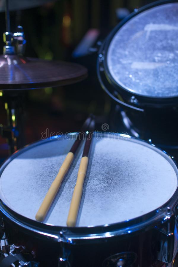 Drum Kit Under Stage Lights. Before the show begins, drum sticks rest over the snare. The drumkit is lit by the blue stage lights stock images