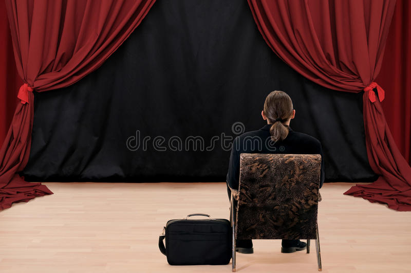 Stage and man. Alone man sitting turn back at stage with red drapery stock photography