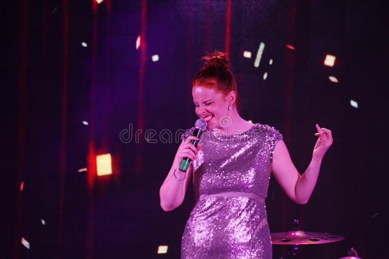 On stage, the musicians pop-rock group Spearmint and singer Anna Malysheva. Red headed Glam Rock Girl singing. On the stage of a nightclub Olympia, Saint stock photo