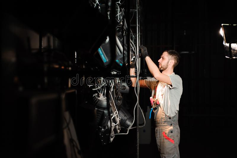 The lighting engineer adjusts the lights on stage behind the scenes stock image