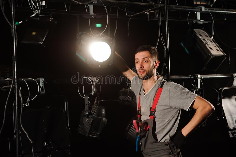 The stage worker sets up the lights. The lighting engineer adjusts the lights on stage behind the scenes royalty free stock photos