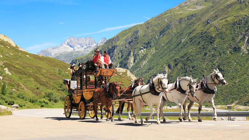 Stagecoach at St. Gotthard Alpine Pass. HOSPENTAL, SWITZERLAND - JULY 18, 2014:Horse-drawn carriage on the way from Andermatt to Airolo on the street Strada royalty free stock photo