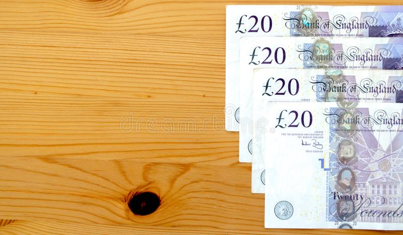 Row of British twenty pound notes on a table royalty free stock photography