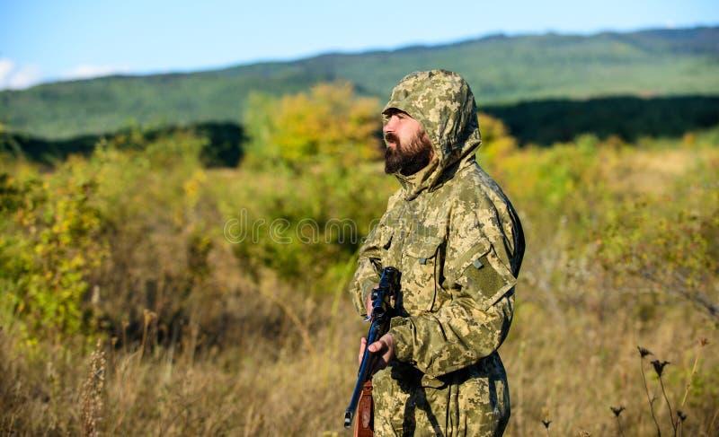Stagione di caccia Cacciatore barbuto dell'uomo con il fondo della natura del fucile L'esperienza e la pratica presta la caccia d fotografie stock libere da diritti