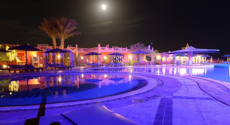 Stagno e patio dell'hotel di località di soggiorno alla notte fotografia stock
