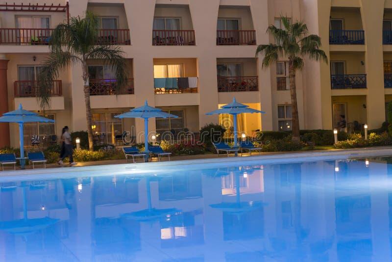 stagno e patio tropicali eleganti alla notte Piscina tropicale nella vista di notte - fondo di vacanza Una piscina della località immagine stock