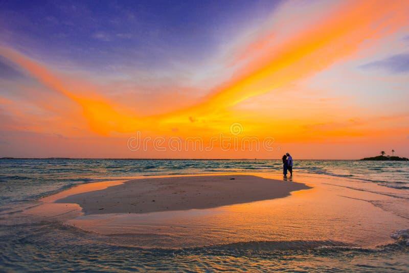 Stagno infinito di tramonto con una coppia fotografie stock