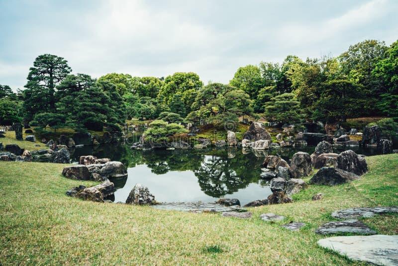 Stagno sereno con le pietre delle rocce nel giardino di Kyoto fotografia stock libera da diritti