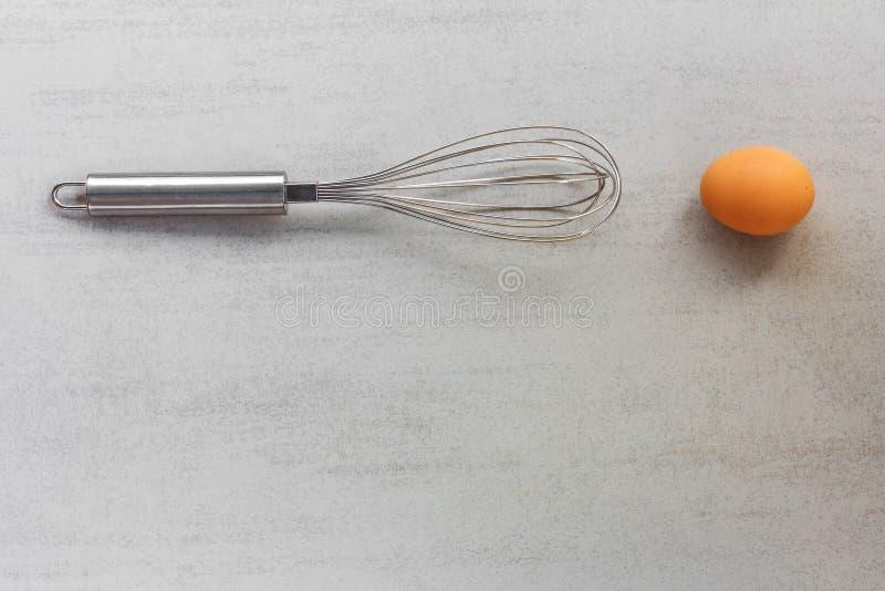 Stahl wischen für das Peitschen und das Mischen und rohes braunes Ei auf einem grauen Hintergrund lizenzfreie stockfotos