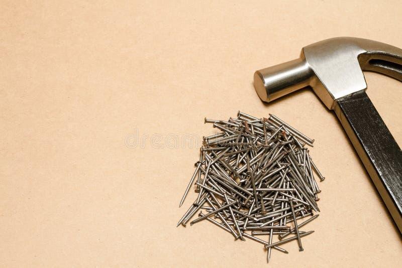 Stahlhammer und Stapel von Nägeln auf braunem Hintergrund stockfotografie