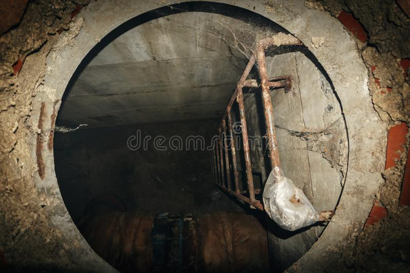 Stahlleiter im technischen Abfall in Untertageabwassersystem, Kanalisationsloch lizenzfreie stockfotos