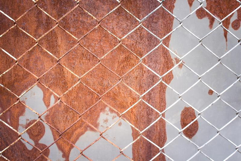 Stahlnettozaunmusterbeschaffenheit auf altem rostigem Zinkhintergrund lizenzfreie stockbilder