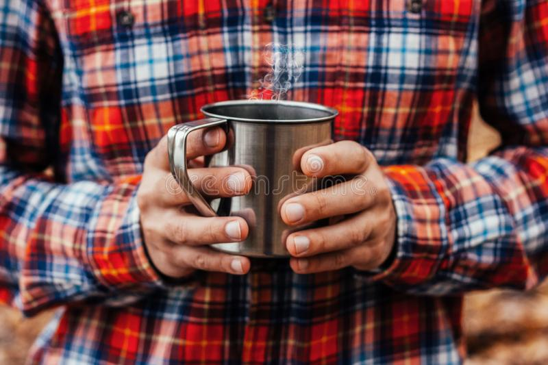 Stahlschale mit einem heißen Getränk in den Händen des Mannes im Herbstpark lizenzfreie stockfotografie