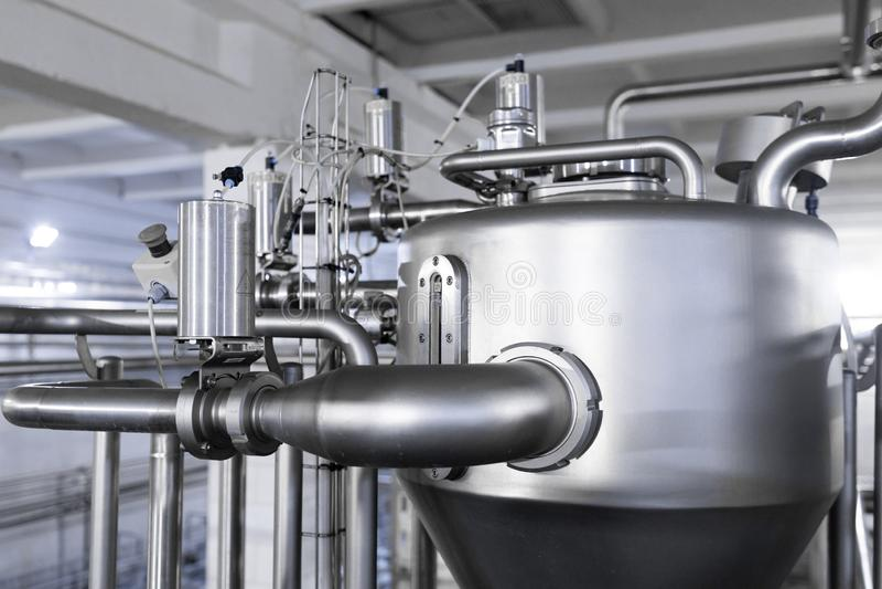 Stahltanks oder Bottiche, Rohrlinien und anderes Ausrüstungswerkzeug in der Betriebswerkstatt stockfoto