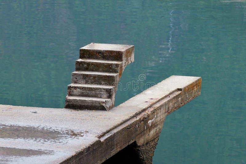 Staicase inacabado sobre a água imagens de stock royalty free