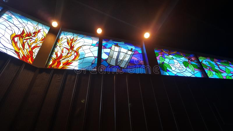 Stain glass in Temple. Stain glass has a bush on fire and a Torah scroll dove also in stain glass royalty free stock photo