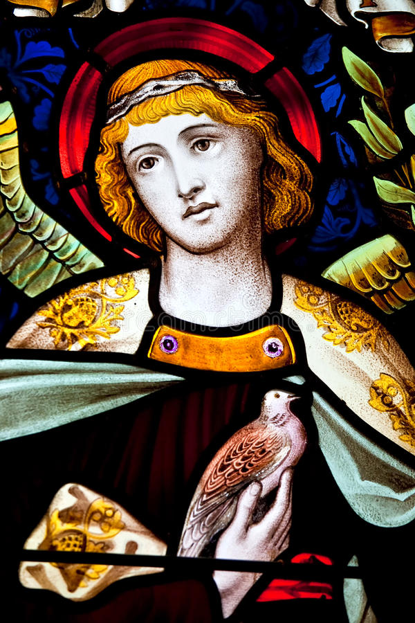 Stained Glass Angel. Detail of a multi colored serene angel in stained glass. From St. Paul's Church (1749), Halifax, Nova Scotia stock image